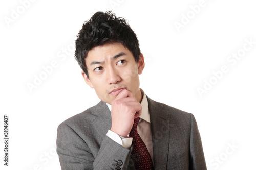 Fotografie, Obraz  顎に手を置いて考えるスーツの男性