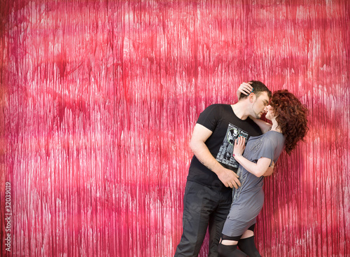 Foto op Aluminium Dance School romantic young couple standing together against red background