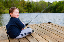 Boy Smiles While Fishing From Dock On Lake.