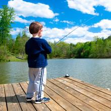 Boy Fishing From Dock On Lake.
