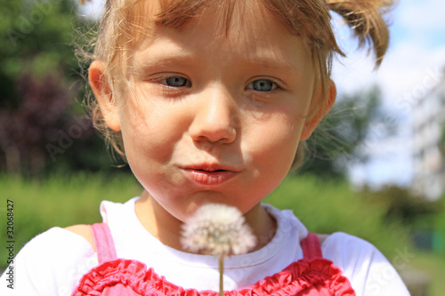 Little girl blowing dandelions on the meadow - 32068427
