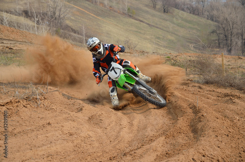 Poster Motocyclette Motocross rider with a strong slope turns sharply