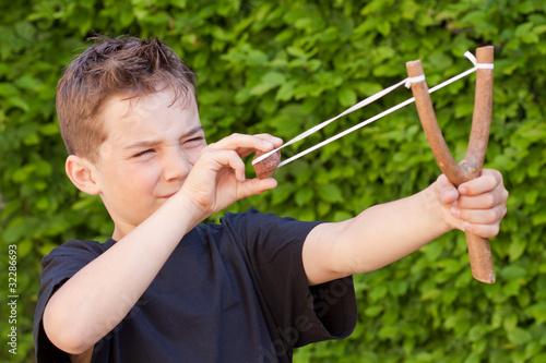 Fotografía  Kind - Junge schießt einen Stein mit der Steinschleuder