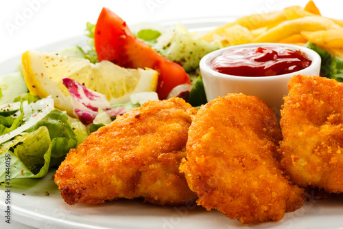 Fototapeta Fried chicken nuggets, French fries and vegetables obraz