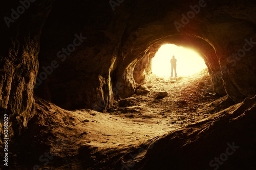 man standing in front of a cave entrance Fototapete