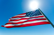 American Flag Waving In The Blue Sky With The Sun Behind