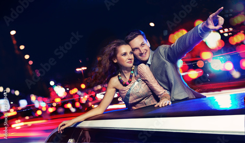 Elegant couple traveling a limousine at night Poster Mural XXL