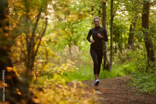 Leinwand Poster Junge Frau beim Joggen im Wald