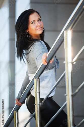 Young woman leaning on the handrail Canvas Print