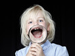 canvas print picture - Blond girl laughing with magnifier in front of her open mouth