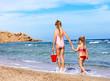 Children holding hands walking on the beach.