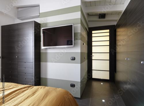 moderna camera da letto con televisore appeso alla parete ...