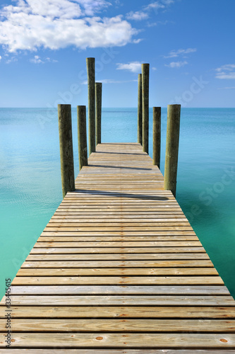 Tuinposter Pier Wooden jetty leading in turquoise blue sea in Governor's Harbour