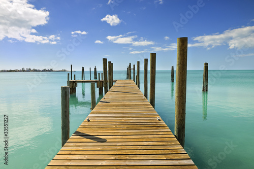 Tuinposter Pier Mooring posts and pontoon leading in turquoise blue sea