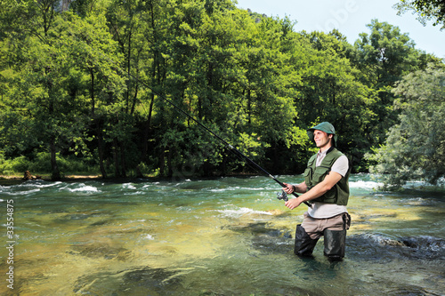 Tuinposter Vissen Fisherman fishing on a river with forest in the background