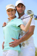a woman with a golf club and a man putting his hands