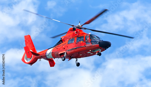 Foto op Canvas Helicopter Red rescue helicopter moving in blue sky