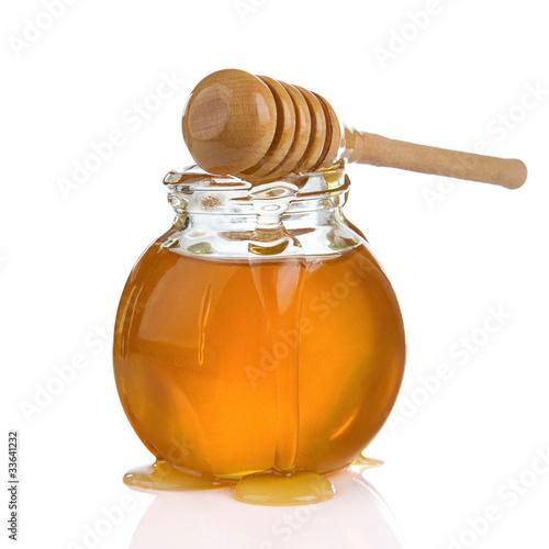 Valokuva  glass jar of honey and stick isolated on white