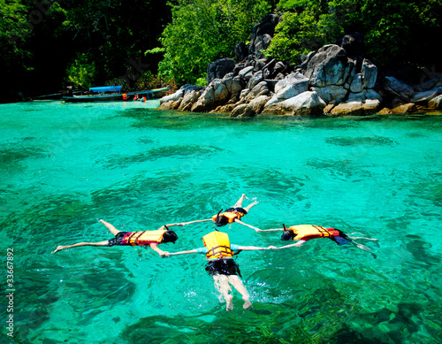 Wall Murals Green coral Snorkeler on surface in Thailand