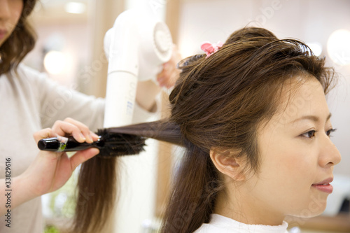 Fotografie, Obraz  ドライヤーで美容師に髪を乾かしてもらう女性