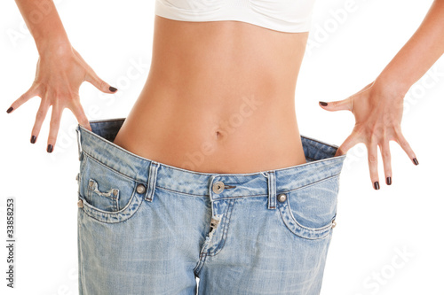 Fotografia  Funny woman shows her weight loss by wearing an old jeans