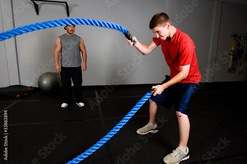Fotografia  Workout with a rope in a gym with a trainer