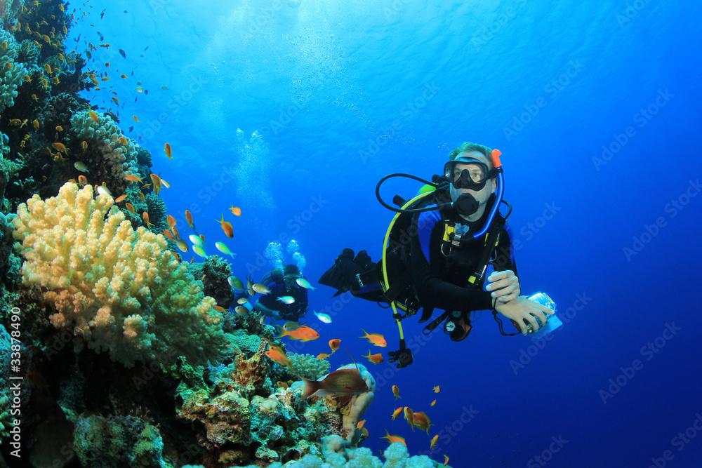 Fototapeta Scuba Diver explores Coral Reef in Tropical Sea
