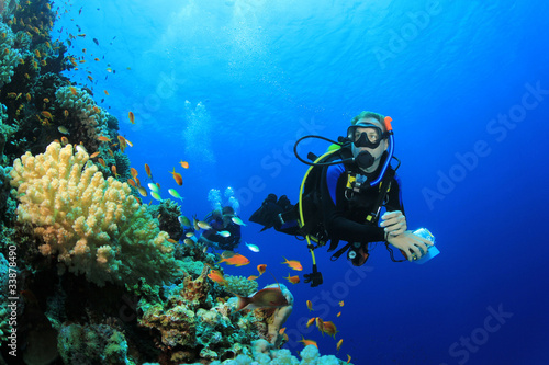 Tuinposter Duiken Scuba Diver explores Coral Reef in Tropical Sea