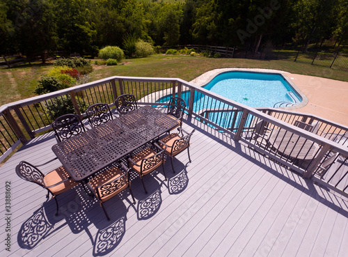 Fotografie, Obraz  Seat and chairs on deck by swimming pool