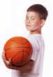 boy in a white vest holds a ball for game in basketball