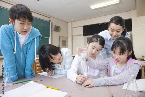 Fotografia  理科の実験をする小学生男女と女性教師