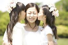 お姉さんの頬にキスする2人の女の子