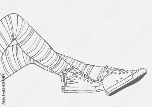 kobiece nogi w pasiastych pończochach i trampkach
