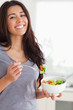 Pretty woman enjoying a bowl of salad while standing