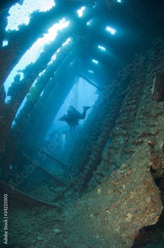 Divers exploring a large shipwreck Canvas Print