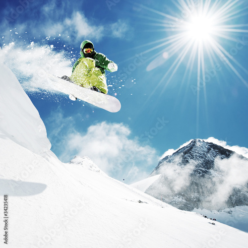 Acrylic Prints Winter sports Snowboarder at jump inhigh mountains