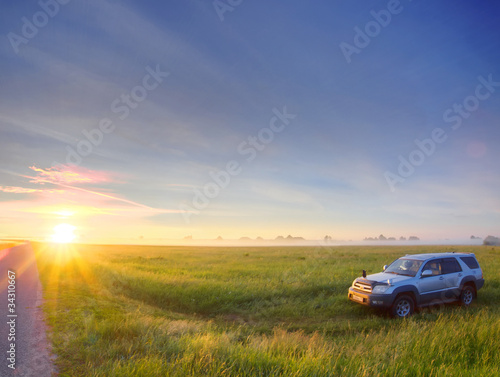 Photo  Car in field on sunset