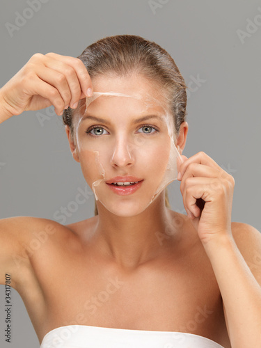 Fotografie, Tablou  young woman taking off peeling mask
