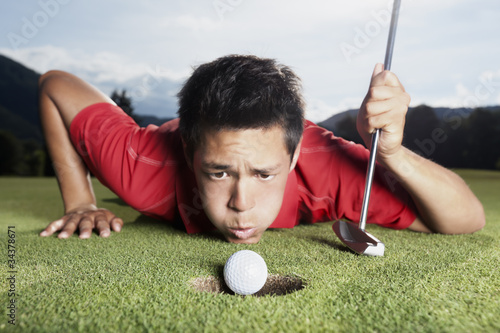 Fotografia, Obraz  Golfer blowing ball into cup.