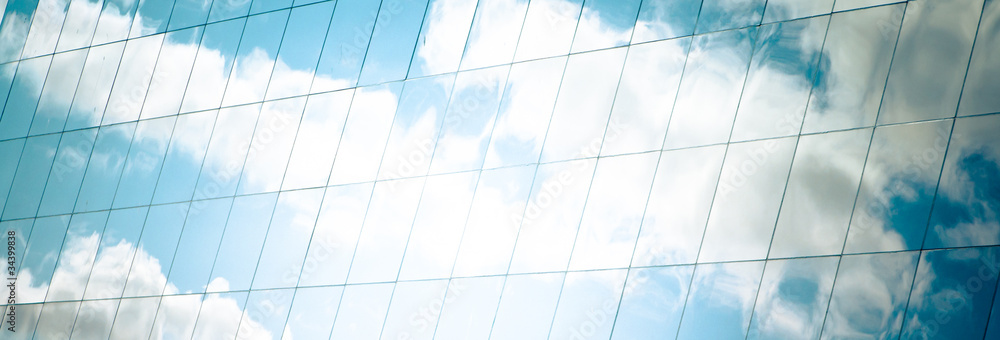 Fototapeta white clouds and azure sky reflected in mirror windows