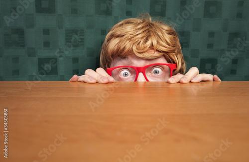 Photo  Scared nerd hiding behind a desk