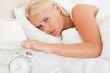 Cute woman awaken by an alarmclock