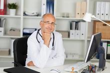 Lächelnder Arzt Am Schreibtisch