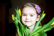 Portrait Of A Sunny Child Girl With Tulips On A Dark Background