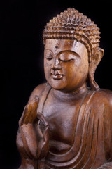 Wooden Buddha on black background