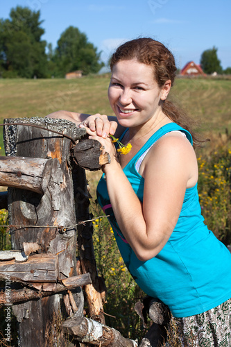 Fotografie, Obraz  One young Caucasian Russian woman near village fence