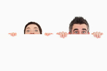 Man And Woman Hiding Behind A White Board With Room For  Copy Sp