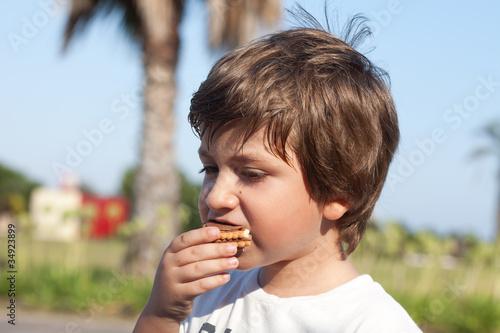 Vászonkép bambino che fa merenda con biscotti e cioccolato