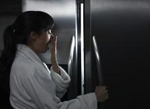 Sleepy Mixed Race Woman Looking In Refrigerator At Night