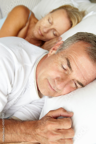 Photo  Head and shoulders mid age couple sleeping